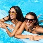 young adult sisters laughing floating in pool