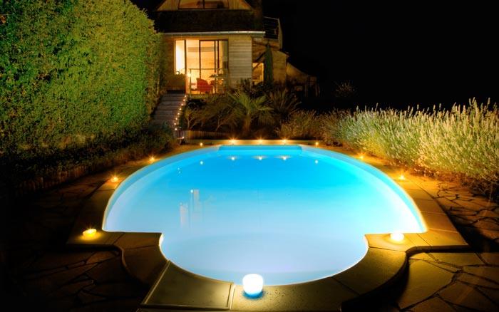Half circle swimming pool in backyard at night
