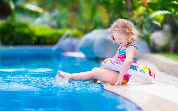 little girl kick splashing water and squinting