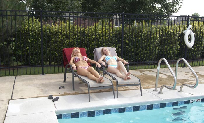 relaxing on lounge chairs in backyard by pool