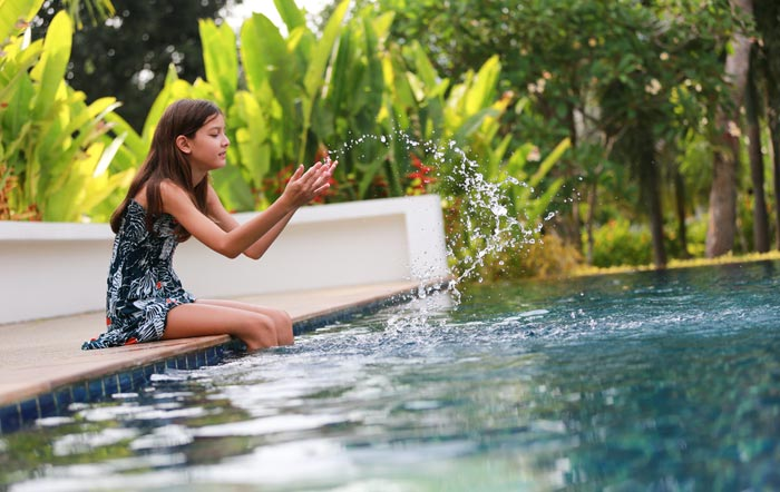 young girl in dress splashing water by pool